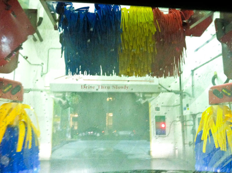 view from front of car during drive through car wash, blue yellow and red wipers