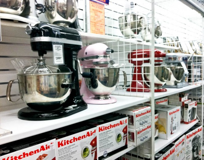 Kitchen aid mixers on shelves with black, pink, and red mixers