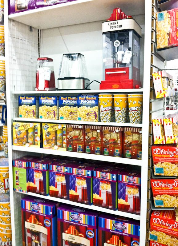 Shelf display of popcorn maker with popcorn and popcorn themed cups