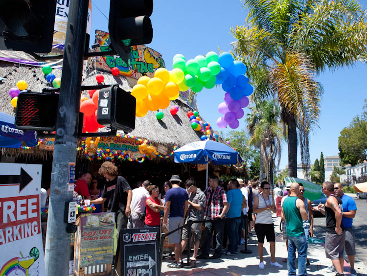 Street corner with Beach hut food stand and free parking signs, rainbow balloons