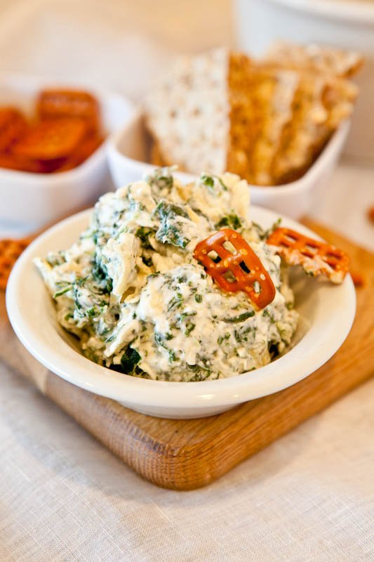 Spinach and Artichoke Dip in white bowl with pretzels dipped in
