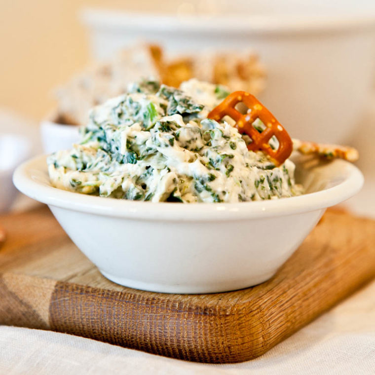 Spinach and Artichoke Dip in white bowl with pretzel dipped in