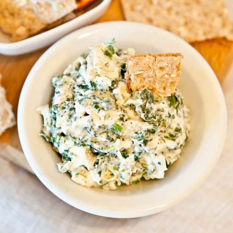 Spinach and Artichoke Dip in white bowl with crackers dipped in