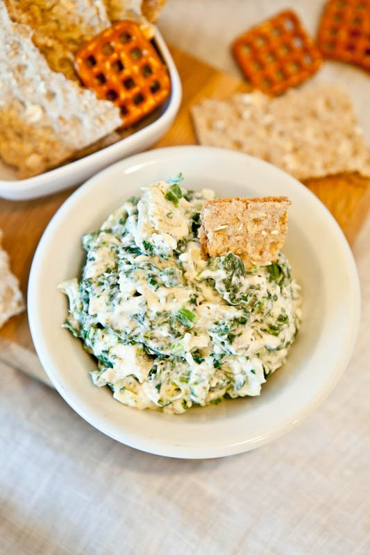 Spinach and Artichoke Dip in white bowl with cracker dipped in and pretzels scattered
