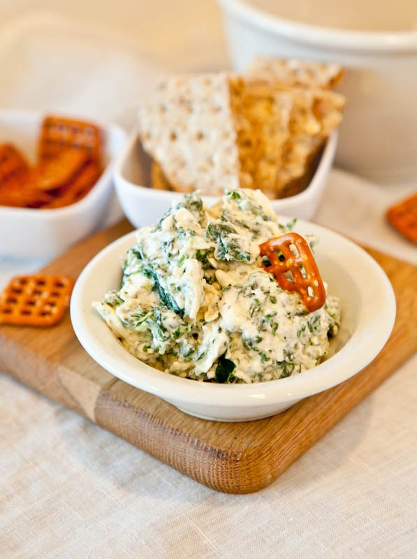 Spinach and Artichoke Dip in white bowl with pretzel dipped in and crackers in background