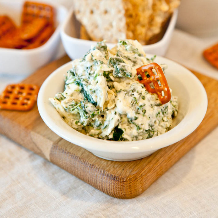 Spinach and Artichoke Dip in white bowl with pretzel dipped in and crackers in the background