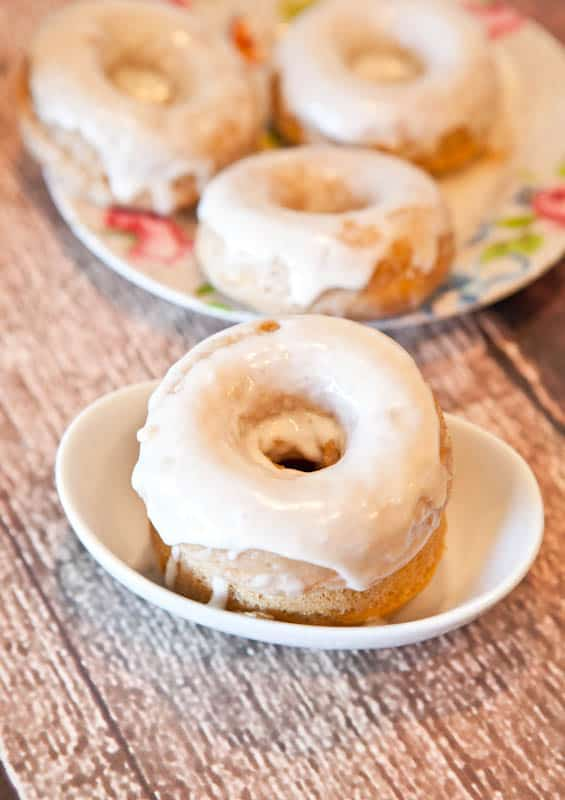 Baked Cinnamon Bun Donuts with Vanilla Cream Cheese Glaze on floral plate and white plate
