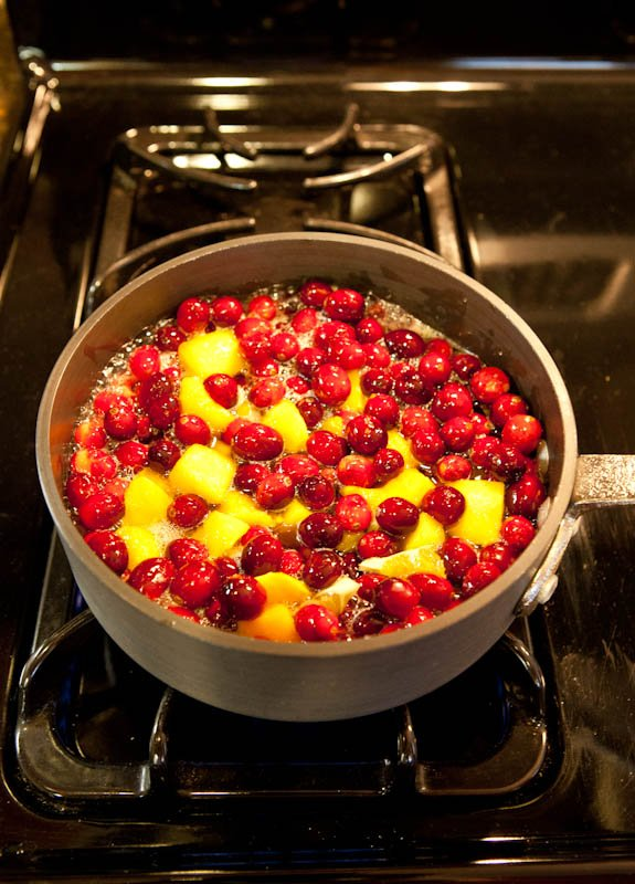 Mango and cranberries simmering in pot on stove