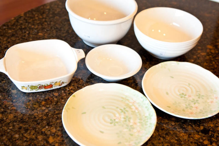 White pans and plates and bowls on marble countertops