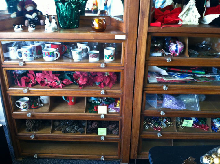 Thrift store cabinets full of mugs and christmas decor