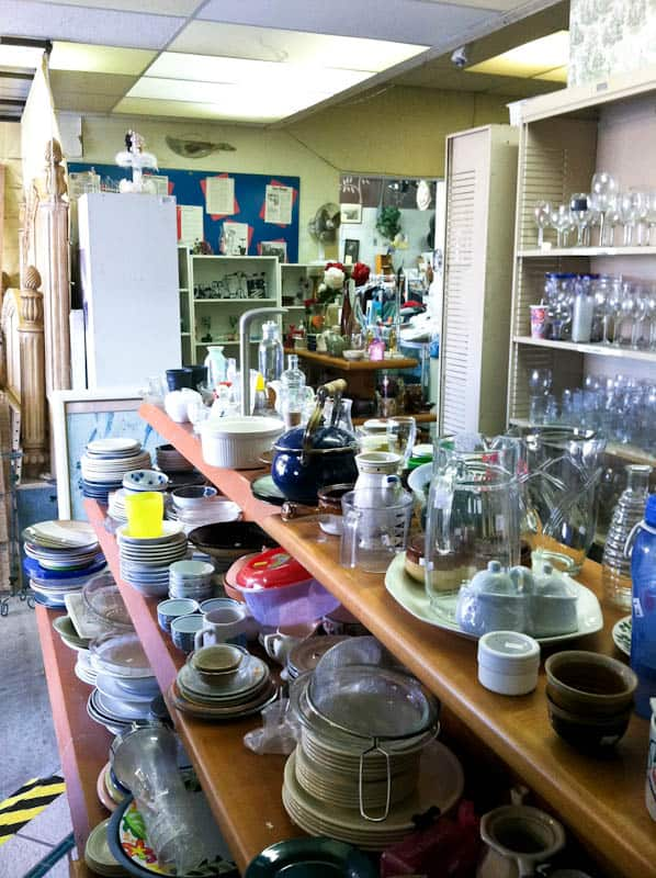 Thrift store shelves with dishes and glasses