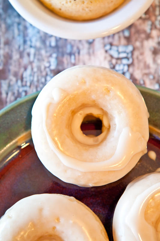 Baked Cinnamon Bun Donuts with Vanilla Cream Cheese Glaze on green and red plate