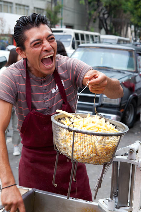 Man laughing holding wire bucket of potato fries