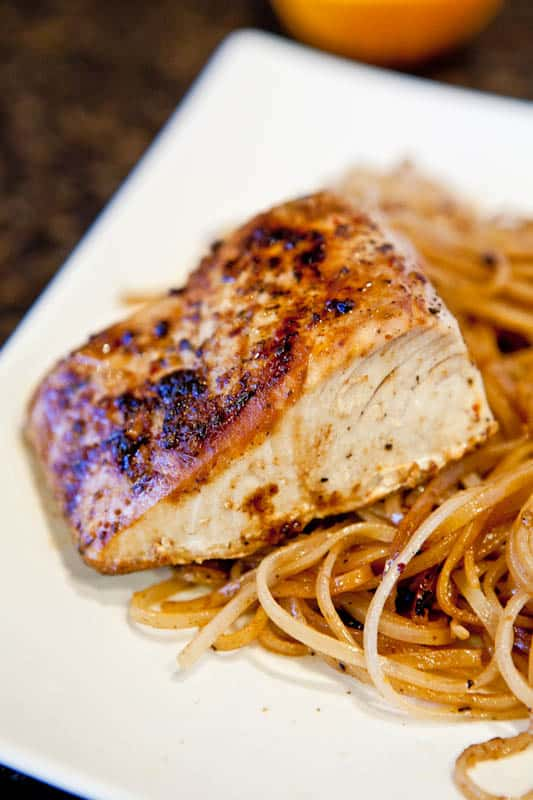 Pan Seared Caribbean Citrus Mahi Mahi with Brown Rice Noodles on a white plate