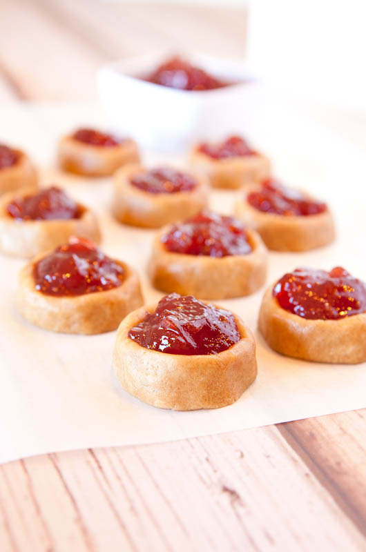 Peanut Butter and Jelly Thumbprint Cookies on parchment paper