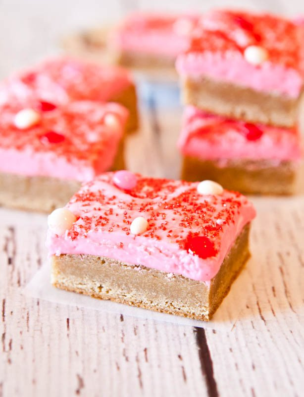 Snickerdoodle Cookie Bars with Pink Vanilla Cream Cheese Frosting on a wooden table