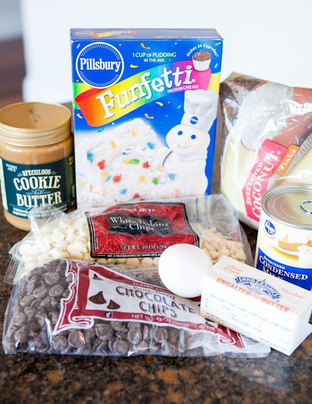 Ingredients spread with funfetti, cookie butter, chocolate chips, condensed milk