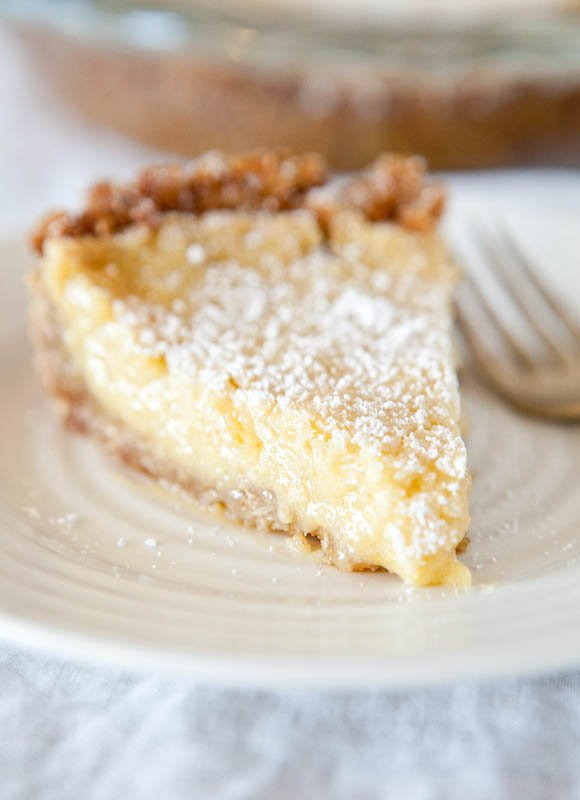 A slice of Crack Pie dusted with powdered sugar on a white plate