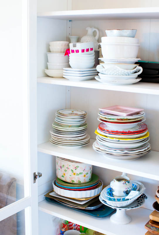 Stacked dishes in white storage cabinet