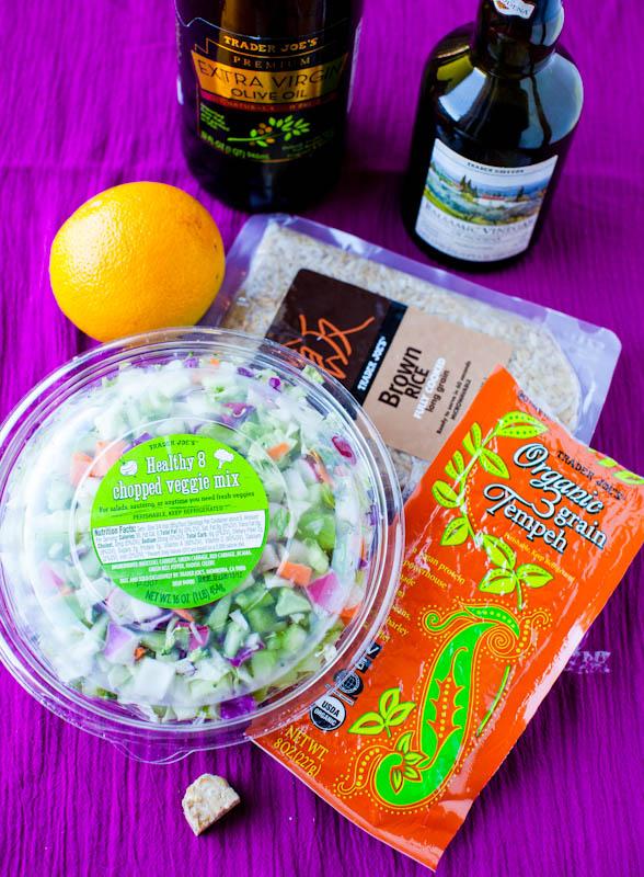 Healthy salad bowl with ingredients tempeh brown rice, orange