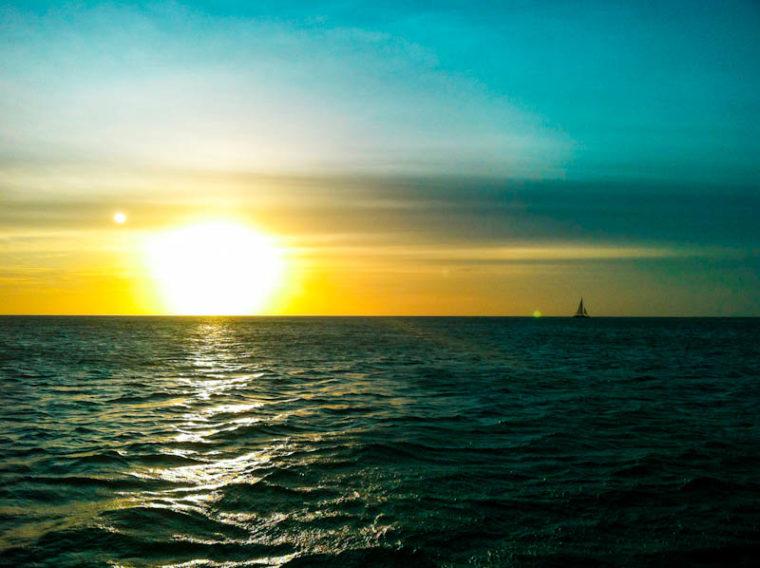 Sun Setting on horizon of ocean