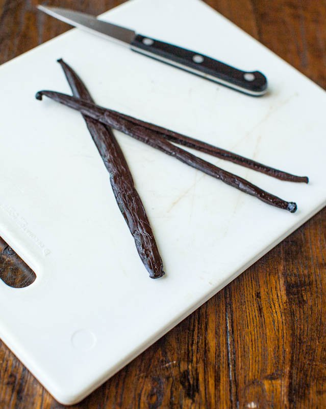 three vanilla beans on white cutting board with knife