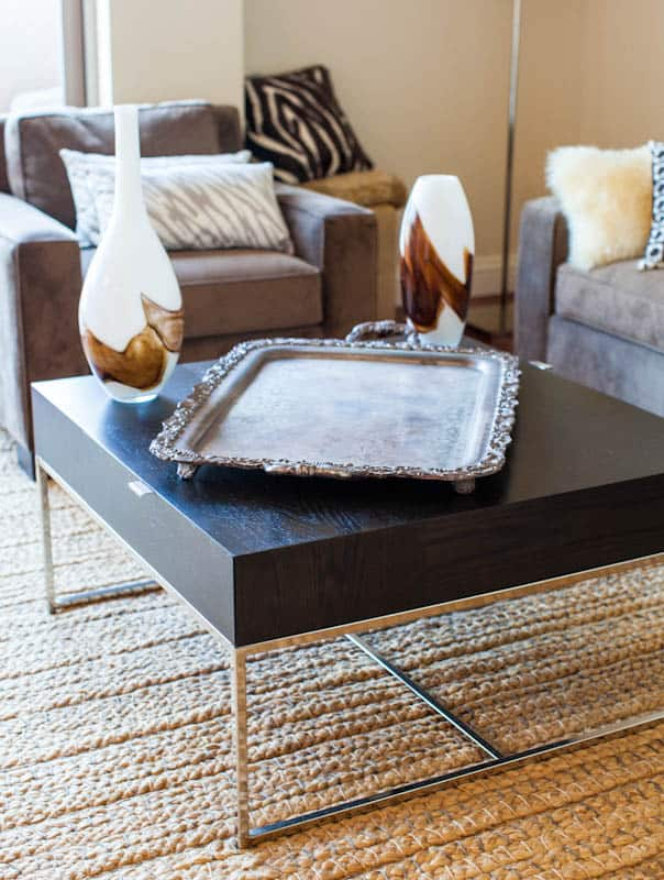 Copper tray on living room coffee table surrounded by couches