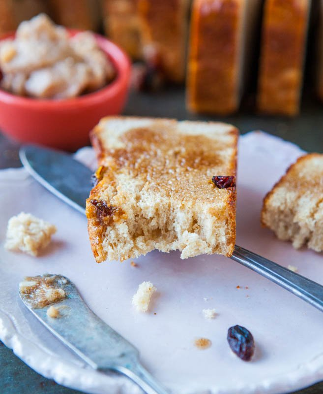 partially eaten slice of english muffin bread on white plat with knife and fork