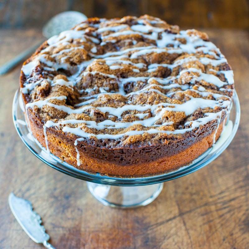 glazed cinnamon streusel coffee cake on a glass cake stand