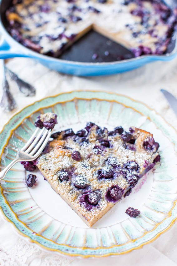 slice of blueberry dutch baby pancake on a plate in front of a skillet