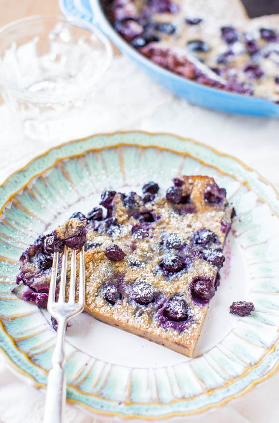overhead view of slice of blueberry dutch baby pancake on plate with fork