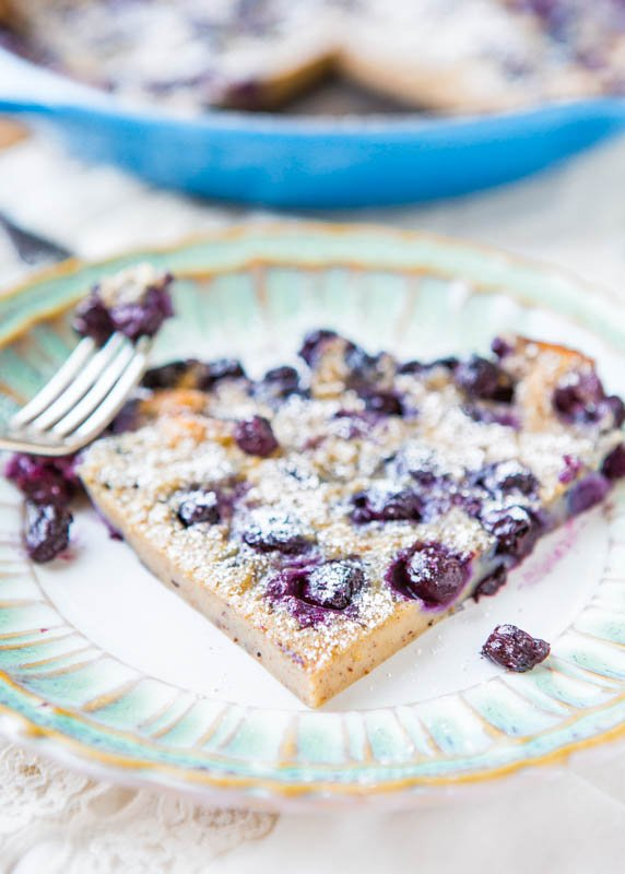 slice of blueberry dutch baby pancake on plate with fork
