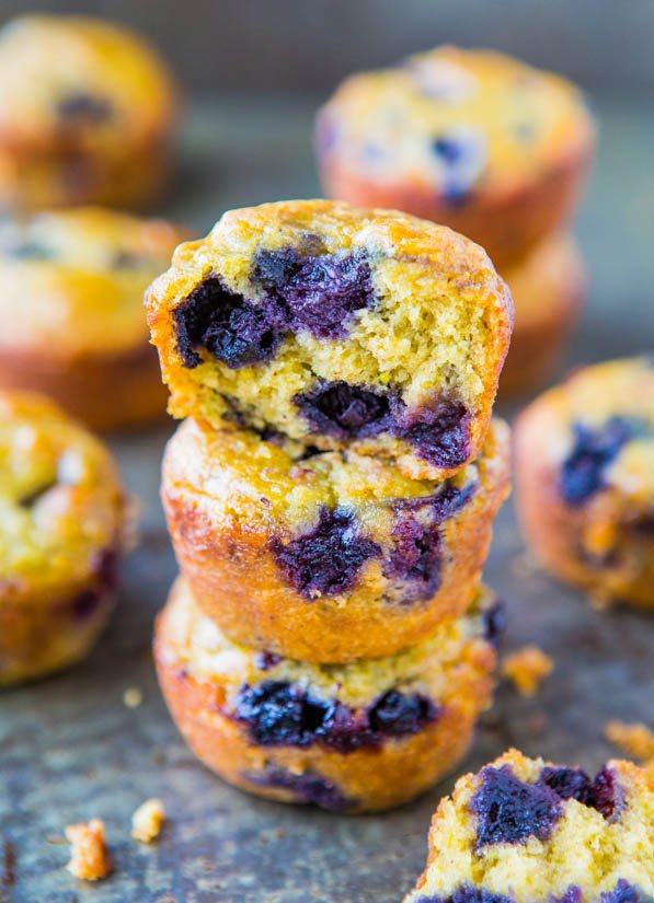 a stack of three Vegan Blueberry Muffins, with the top muffin missing a bite