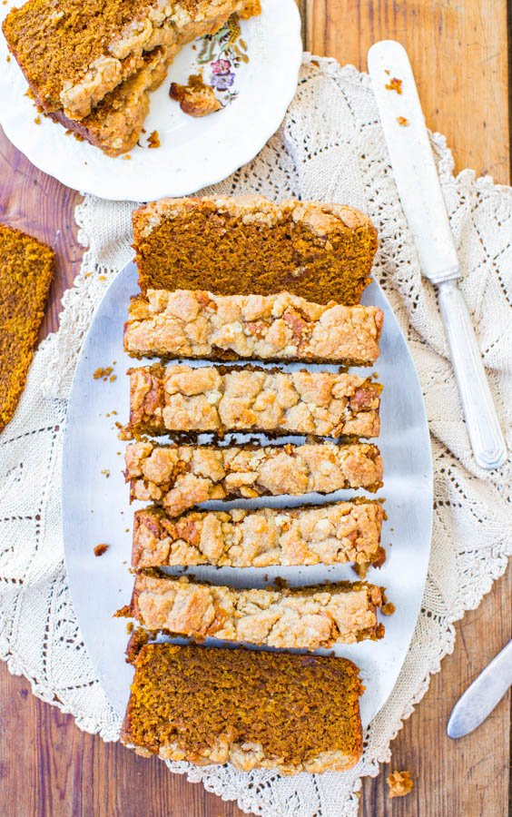 overhead view of sliced loaf of vegan pumpkin bread with streusel topping on a white platter