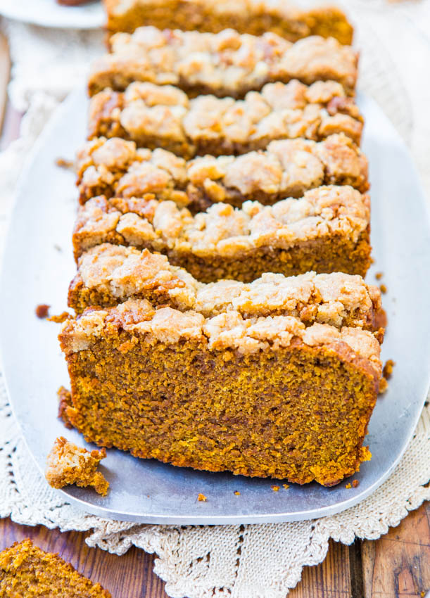 sliced loaf of vegan pumpkin bread with streusel topping on a white platter