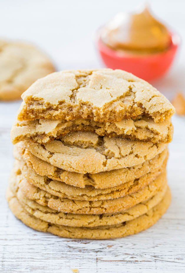 Big Soft and Chewy Peanut Butter Crinkle Cookies stacked on plate with one split in half