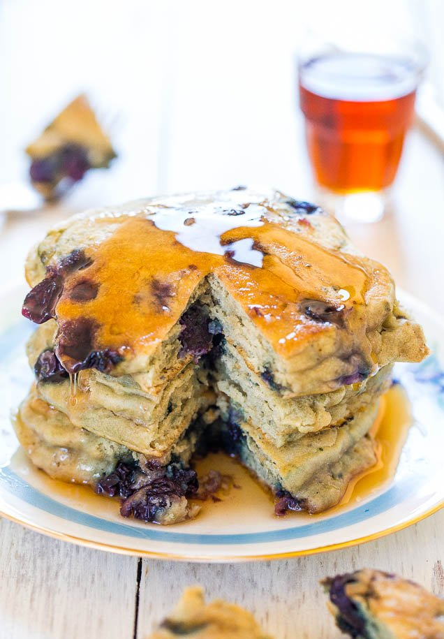 Soft & Fluffy Blueberry Pancakes with bite taken out of stack