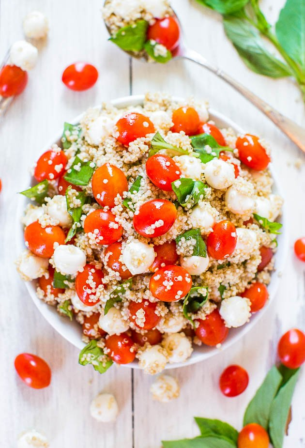 Tomato Mozzarella Salad with Basil and Quinoa in large bowl with spoon