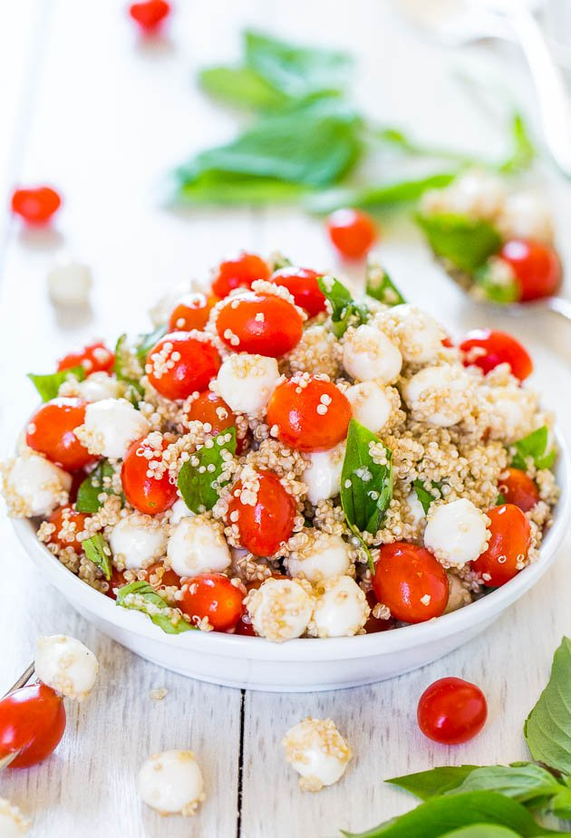 Tomato Mozzarella Salad with Basil and Quinoa with basil leaves and cherry tomatoes in background