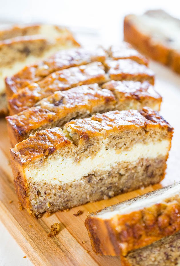 Cream Cheese-Filled Banana Bread slices on a wooden cutting board.