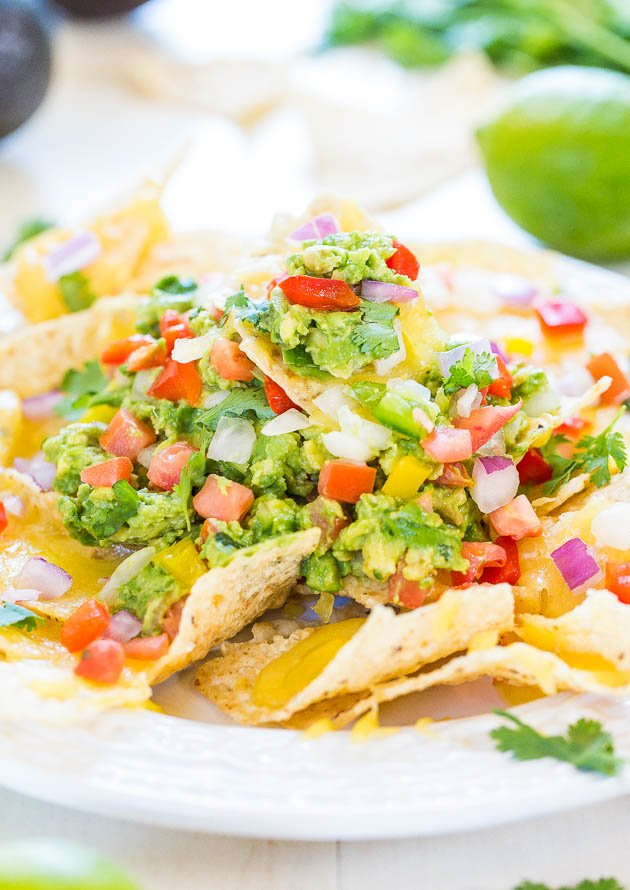 Loaded Guacamole Nachos - Fresh, easy homemade guac on top of cheesy chips is totally irresistible! These disappear fast - so good!!