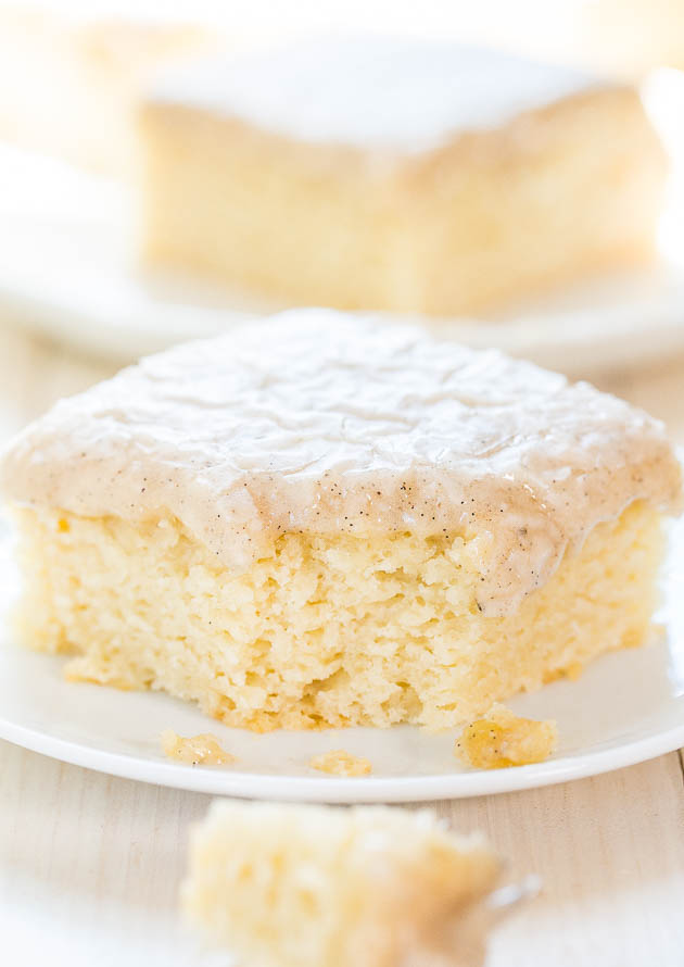 slice of moist vanilla cake with vanilla glaze with bite missing on a plate