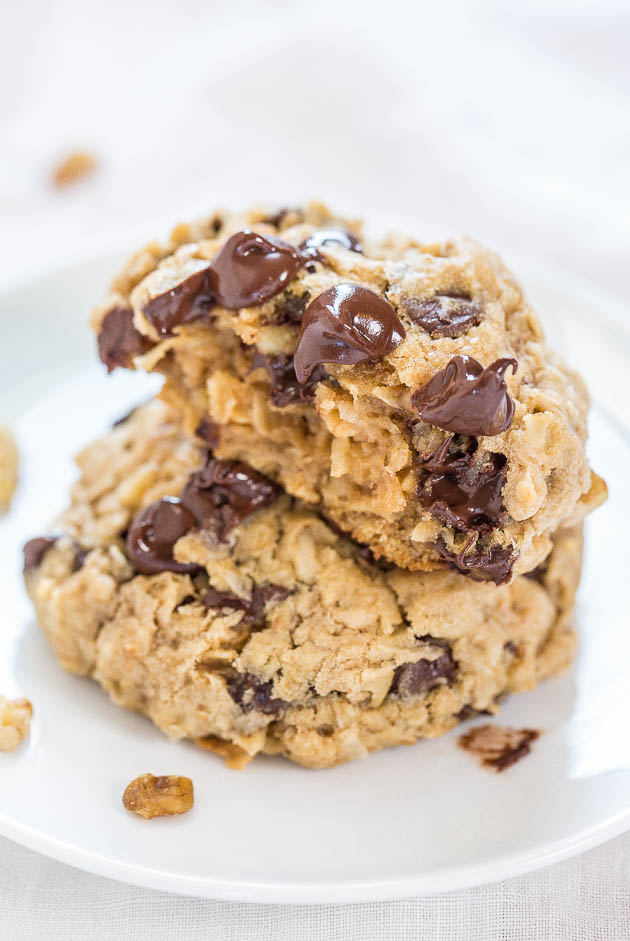 two oatmeal coconut chocolate chip cookies stacked on a white plate