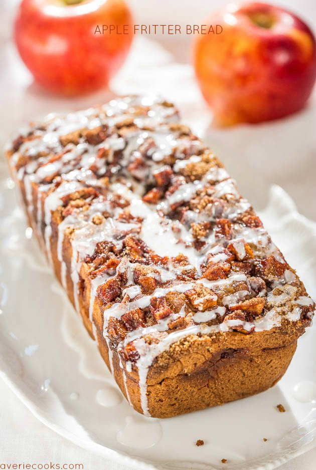loaf of apple cinnamon bread on a white platter. Two apples stand in background.