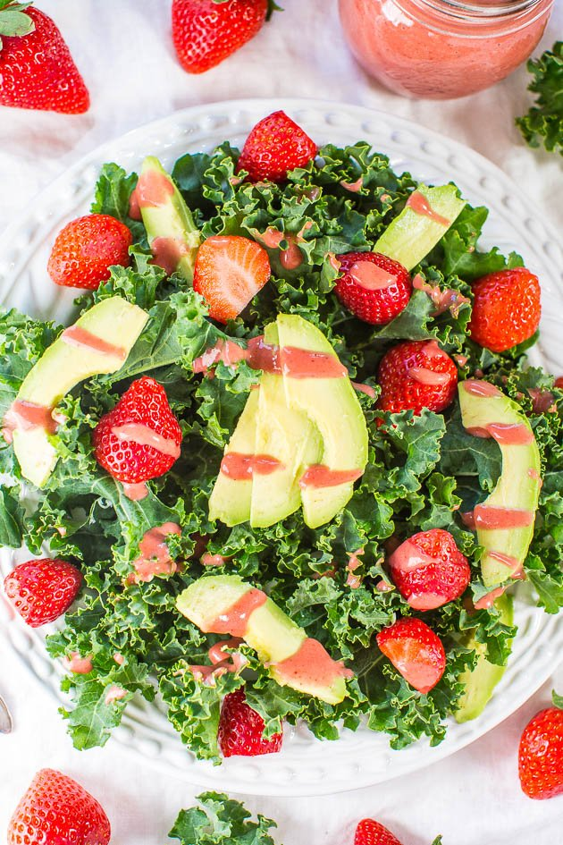 overhead view of kale strawberry salad drizzled with strawberry dressing