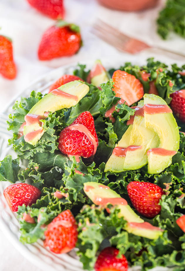strawberry avocado salad in a glass bowl with berries in the background