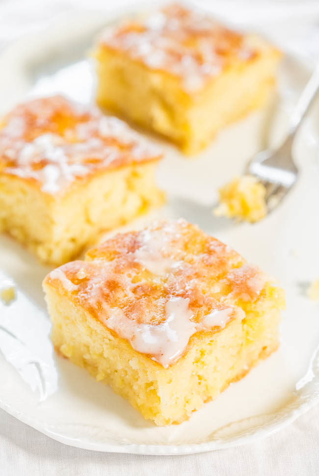 Pineapple Poke Cake with Pineapple Glaze on a white plate