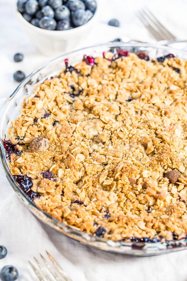 Blueberry Crisp in pie dish with bowl of fresh blueberries in the background