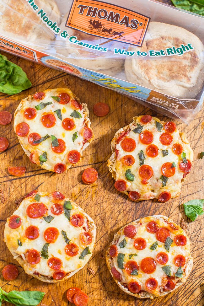 four english muffin pizza on cutting board next to package of english muffins