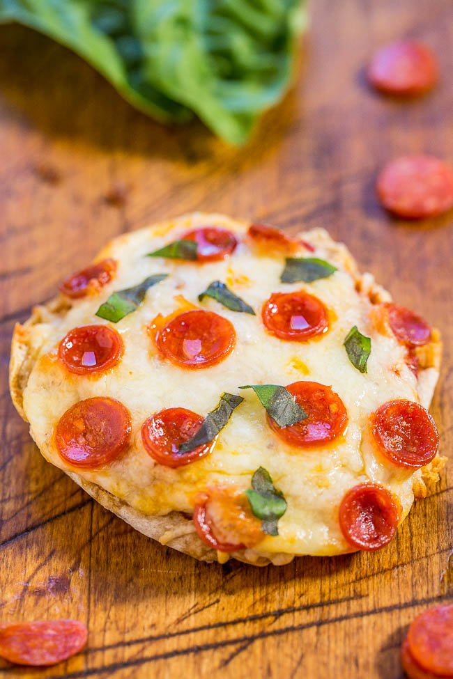 close up of a english muffin mini pizza topped with mini pepperoni and basil